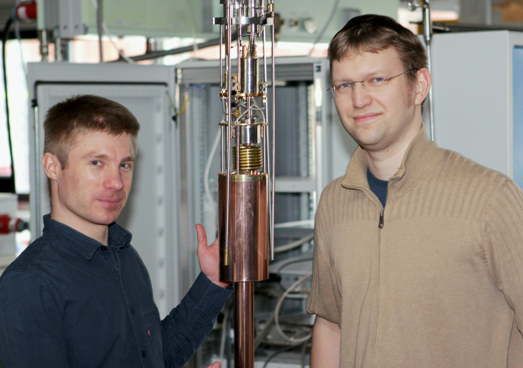 The researchers and their most important instrument: Alexander Steppke (left) and Stefan Lausberg, the main authors of the current study, with a dilution refrigerator via which they attain temperatures in the neighbourhood of absolute zero.