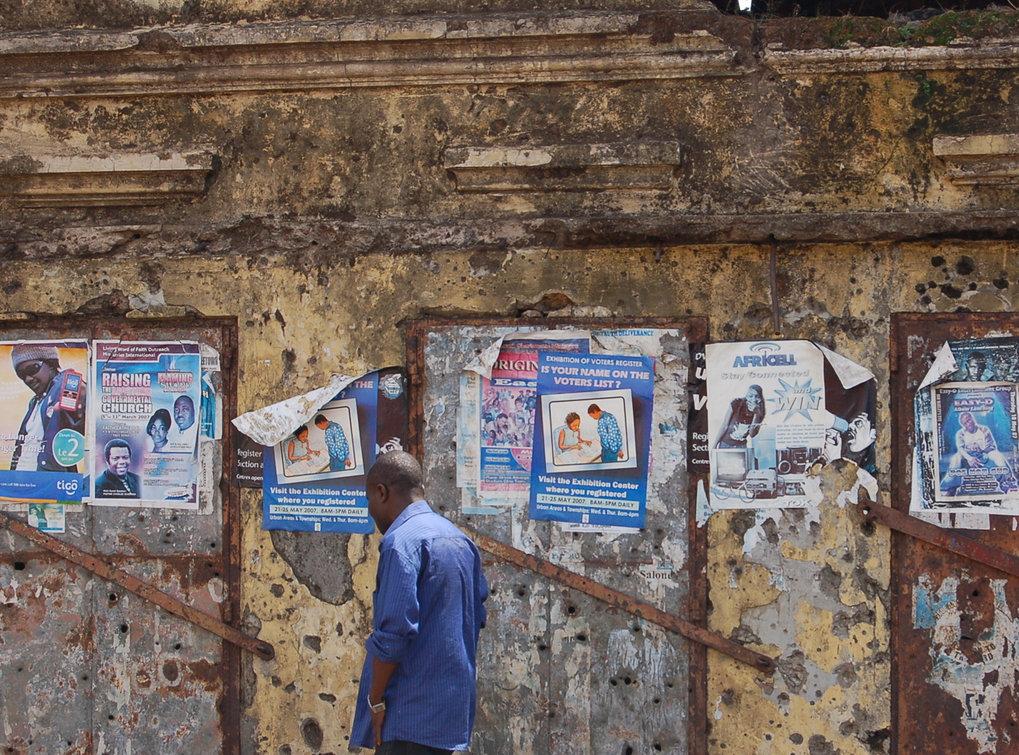 Abb. 2: Freetown, diverse Plakate auf Englisch, die unter anderem zur nationalen Wahl, zum Besuch von Gottesdiensten und Konzerten sowie zum Abschluss