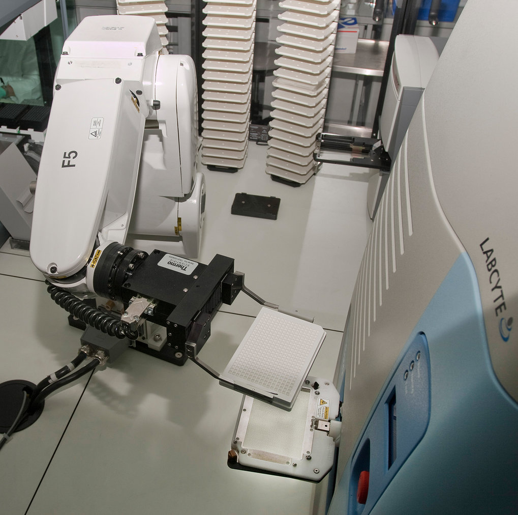 Abb. 2:Der Robotergreifarm überführt eine Testplatte in denakustischen Nanoliter-Dispensierer.