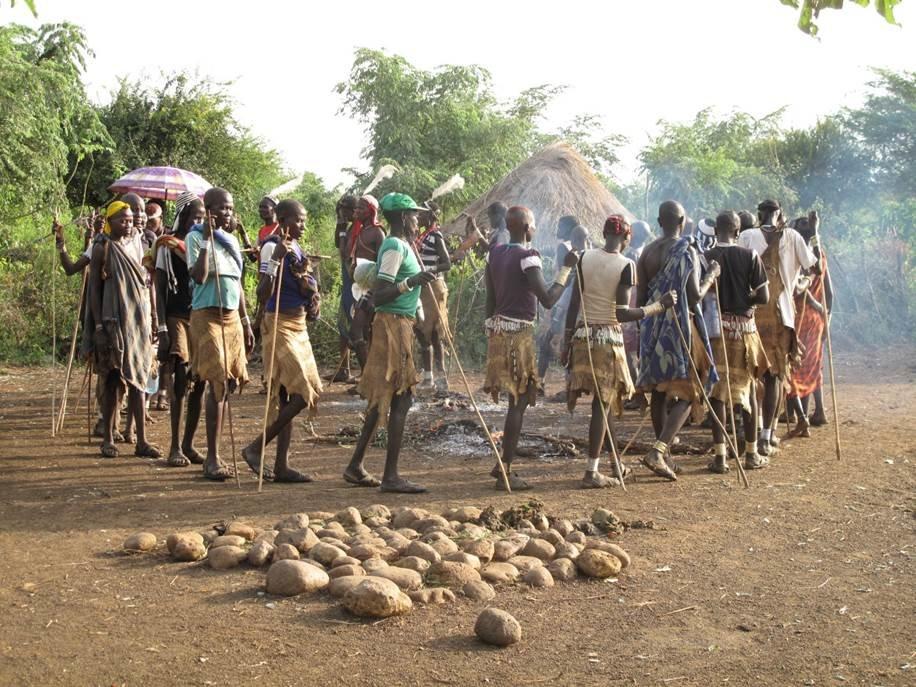 Abb. 2: Neben einer rituellen Steinplattform umrunden Mela ein Feuer, auf dem das Fleisch eines geopferten Ochsen gebraten wird.