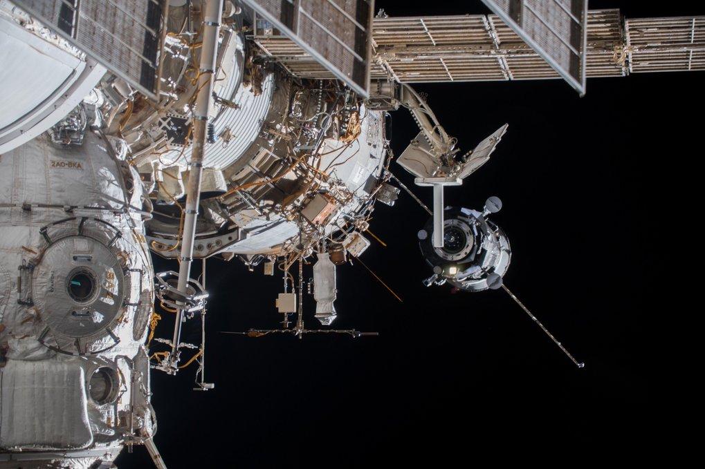 Eine Sojus-Kapsel nähert sich der ISS, im Vordergrund ist die stabförmige Icarus-Antenne zu sehen.