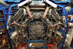 The ATLAS detector (A Toroidal LHC ApparatuS). Axial view of the central part about two years before completion of installation in its underground cavern. The people to the lower left demonstrate its size.