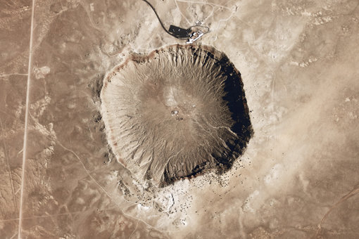 Barringer Crater, also known as Meteor Crater, in Arizona. This crater was formed around 50,000 years ago by the impact of a nickel-iron meteorite. Near the top of the image, the visitors center, complete with tour buses on the parking lot, provides a sense of scale.