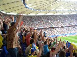 La Ola im Fußballstadium. Ein Teil der Zuschauer steht auf und wirft die Arme hoch. Diese Bewegung kann wie ein Tsunami durch die Tribüne laufen.