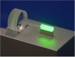 Squeezed light source: a crystal that is illuminated with green light places photons of an infrared laser beam (not visible) in a specific order, thereby reducing the photon noise in that infrared laser.
