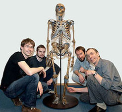 The Neanderthal genome research group: Johannes Krause, Adrian Briggs, Richard E. Green, Svante Pääbo (from left to right). In the middle of the photo: a Neanderthal skeleton