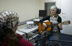 Two musicians are playing a duet. With the help of the electrodes attached to their heads, scientists measure the brain activity of the guitarists. <br /><br />