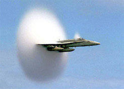 "A commonly encountered shock wave is the sonic shock produced by supersonic aircraft, such as this US navy jet on a fast low flyby over the sea. As a supersonic jet exceeds the speed of sound (or Mach 1), it catches up with its own sound waves. The sound waves become compressed together into a cone-shaped ""shock"" which travels outwards towards the ground, producing the familiar ""sonic boom"". The sonic shock is invisible to us, but its presence can sometimes be revealed in humid conditions by the condensation of water vapour into droplets in the flow downstream of the shock, forming a conical cloud behind the tail of the jet."