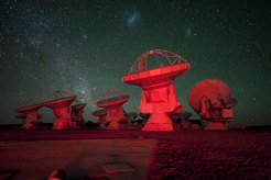 A number of ALMA antennae bathed in red light seen against the Chajnantor night sky. In the background there is the southern Milky Way on the left and the Magellanic Clouds at the top.