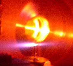 The purple light originates from helium atoms excited by intense laser light. The laser pulses propagate along the axis of the purple lobes (horizontally) through the helium gas, and the X-ray beam (not visible) is radiated in a beam several hundred micrometers in diameter in the same direction.