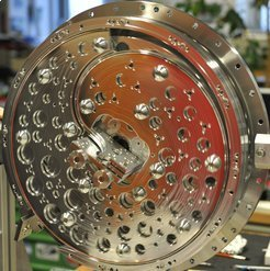 Deceleration in the centrifuge: Molecules lose speed drastically when they are guided against the centrifugal force to the centre of a rotating disk. Electrodes guide the particles to the centre of the centrifuge. The rotating electrodes are likewise designed as disks to ensure mechanical stability. The edges of the disks act like electrostatic guiderails for the molecules. Seen here are the inwardly bent electrodes that are used to guide the particles to the rotation axis. The electrode disks aren't symmetric with respect to the centre of the disk, so the holes in them balance them out to prevent any imbalance during rotation.