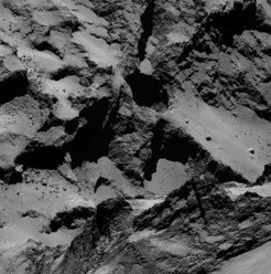 "The pits allow for a look up to 200 meters into the comet. The inner walls show layered structures. These pits can be found on the ""back"" of the comet"