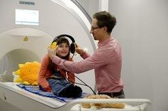 With the help of a model brain scanner, a young volunteer is preparing for the experiment. Michael Skeide, researcher at the Child Language Laboratory
